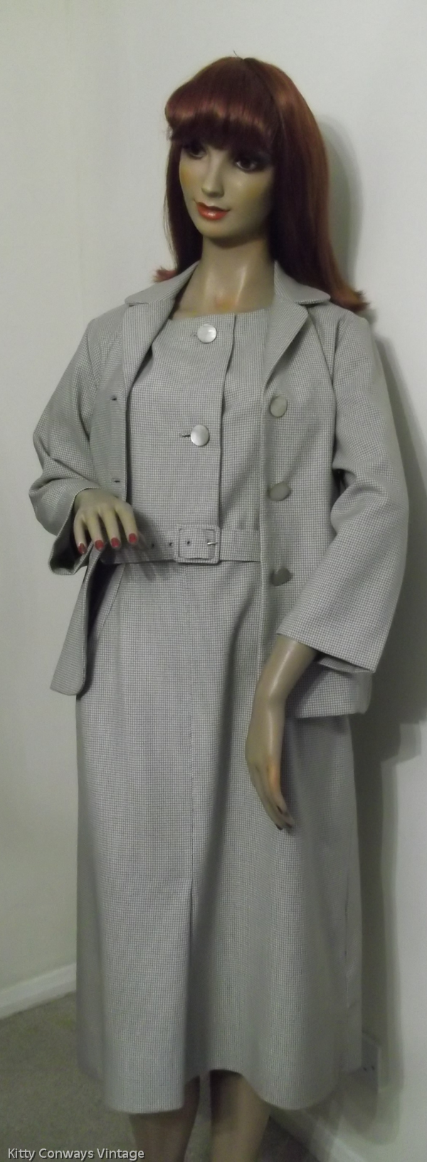 On mannequin with jacket unfastened to show dress