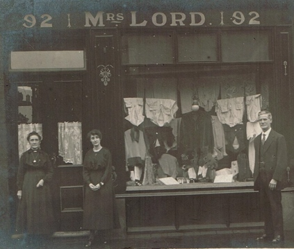 c1910s/1920s shop front with full window display and the owners stood at either side.