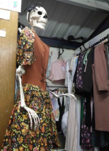 Full size skeleton in a 1970s dress in front of stall with new stock