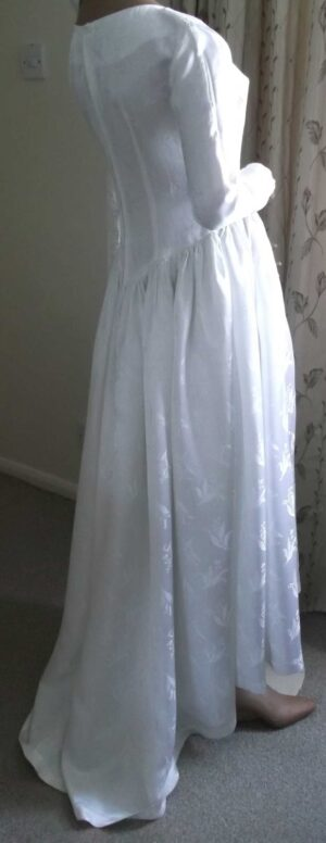 Side and partial back view of the wedding dress showing the train