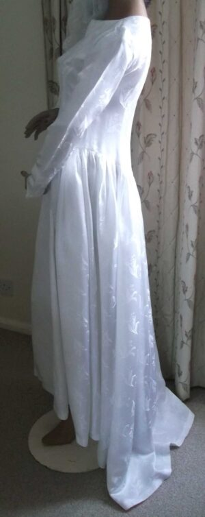 Side view of the wedding dress showing medieval sleeve and train