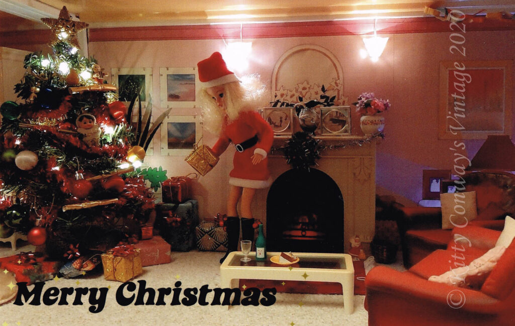 A Sindy doll ina Santa outfit places a present beneath a miniature Christmas Tree - 1970s text states Merry Christmas