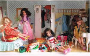 1970s and 80s Sindy dolls search through a messy bedroom to find items to pack in bulging suitcases.