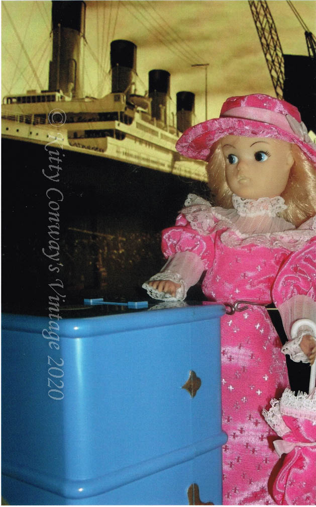 Blonde Sindy stands in a pink Edwardian style dress with her blue steamer trunk in front of an image of the Titanic