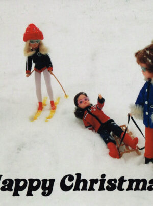 Four Vintage Sindy dolls play in the snow. One has fallen off a slegde held by a 1960s doll, while 1980s skiing Sindy and 60s Paul look on.